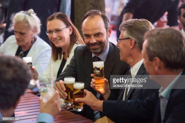 French Prime Minister Edouard Philippe drinks a beer as he supports La Republique en marche party's candidates for the legislative elections in the...