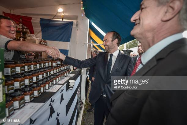 French Prime Minister Edouard Philippe escorted by French lawmaker Jean Lassalle shakes hand with a caramel and tofee exhibitor from the Brittany...