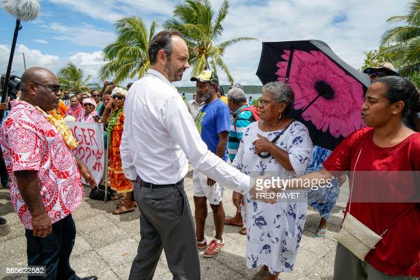 French Prime Minister Edouard Philippe greets local residents gathered for a demonstration against oil pollution in the town of We on Lifou Island on...