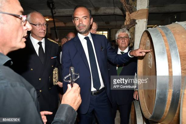 French Prime Minister Edouard Philippe is shown a barrel during his visit to Domaine du Grand Comté in Roquelaure south western France on August 18...