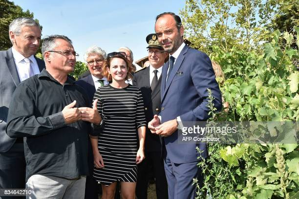 French Prime Minister Edouard Philippe listens to wine and armagnacs producer Michel Baylac as they stand in a vineyard during his visit to Domaine...