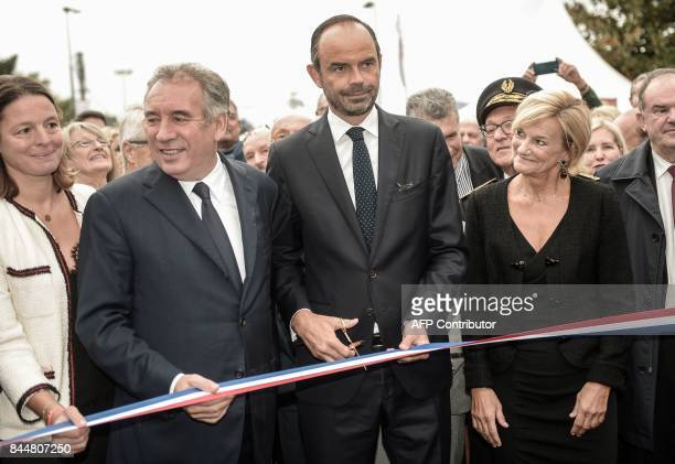 French Prime Minister Edouard Philippe prepares to cut the ribbon as he inaugurates along with and Pau mayor and former Justice Minister Francois...