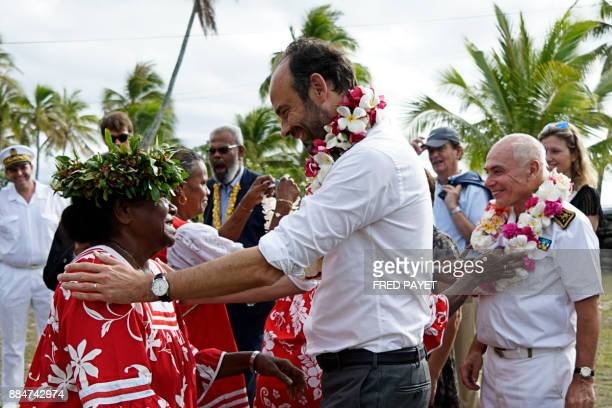 French Prime Minister Edouard Philippe reacts after receiving a flower neklace during a welcoming ceremony at the Tiga chiefdom on Tiga island in the...