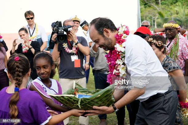 French Prime Minister Edouard Philippe receives a gift as he meets pupils and teachers of the public school on Tiga island in the archipelago of the...