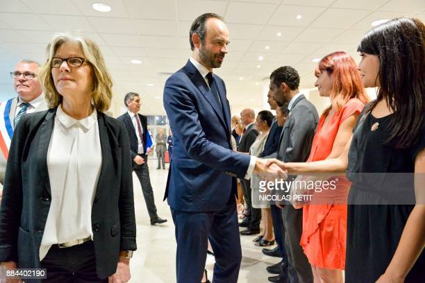 French Prime Minister Edouard Philippe shakes hands with delegates next to Noumea's Mayor Sonia Lagarde as he arrives for a meeting during his visit...