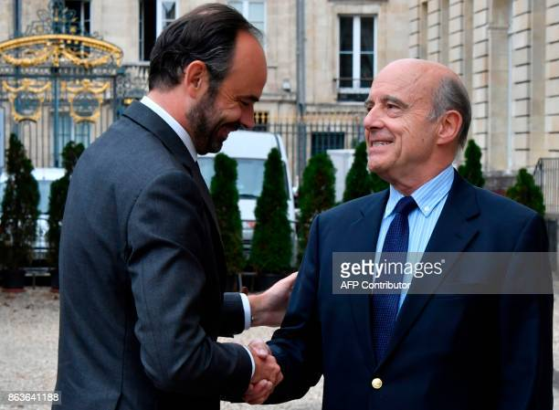 French Prime Minister Edouard Philippe shakes hands with former Prime Minister and current Mayor of Bordeaux Alain Juppe as he arrives at The Town...