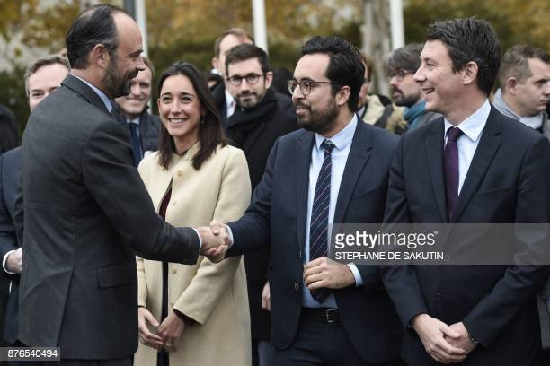 French Prime Minister Edouard Philippe shakes hands with French Junior Minister for the Digital Sector Mounir Mahjoubi next to French Junior Minister...