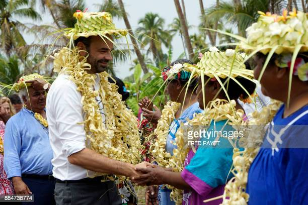 TOPSHOT French Prime Minister Edouard Philippe shakes hands with residents and members of the Drueulu tribe during a welcoming ceremony at the Case...