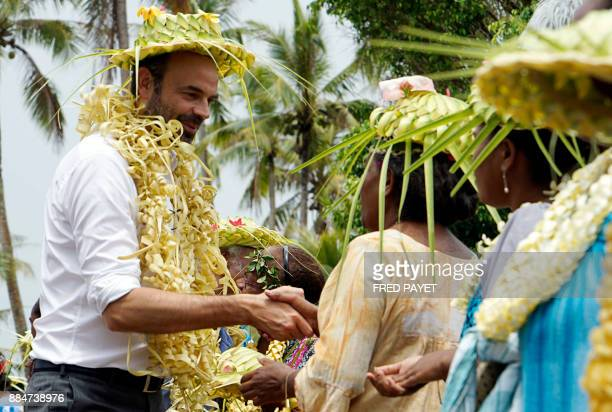 French Prime Minister Edouard Philippe shakes hands with residents and members of the Drueulu tribe during a welcoming ceremony at the Case de la...