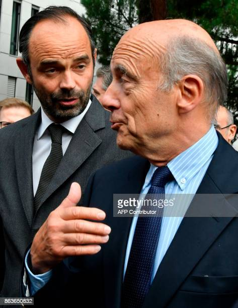 French Prime Minister Edouard Philippe shares a light moment as he walks with former Prime Minister and current Mayor of Bordeaux Alain Juppe as they...