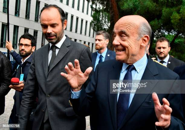 French Prime Minister Edouard Philippe shares a light moment with former Prime Minister and current Mayor of Bordeaux Alain Juppe as they walk...