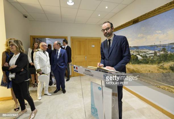 French Prime Minister Edouard Philippe signs a visitor's book as he arrives for a meeting with Noumea's Mayor Sonia Lagarde during his visit in...