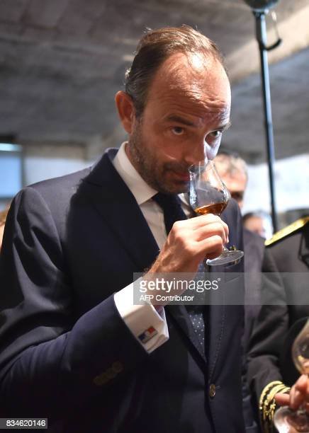 French Prime Minister Edouard Philippe smells a glass of armagnac before tasting during his visit to Domaine du Grand Comté in Roquelaure south...