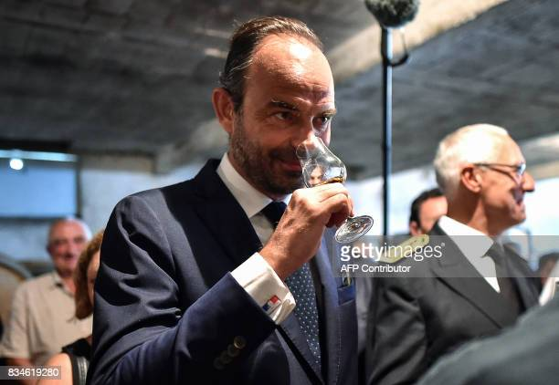 French Prime Minister Edouard Philippe smells the a glass of armagnac before tasting during his visit to Domaine du Grand Comté in Roquelaure south...