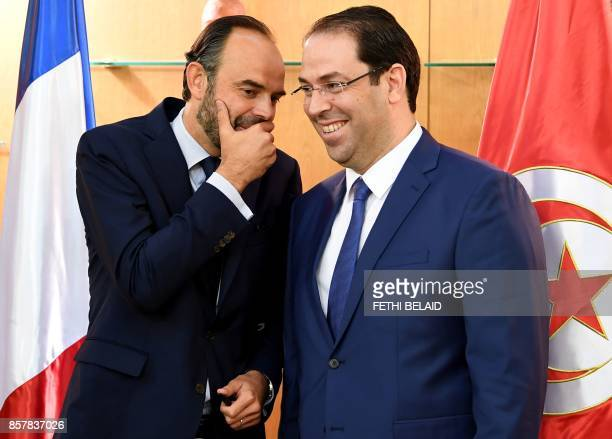 French Prime Minister Edouard Philippe speaks with his Tunisian counterpart Youssef Chahed prior to giving a press conference following a meeting in...
