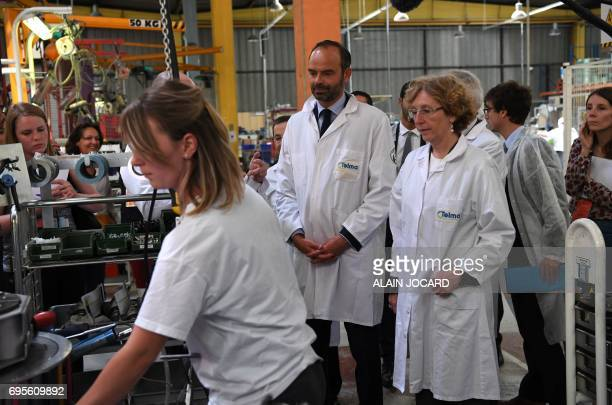 French Prime Minister Edouard Philippe stands next to Minister of Labour Muriel Penicaud during their visits to the Telma plant that manufactures...