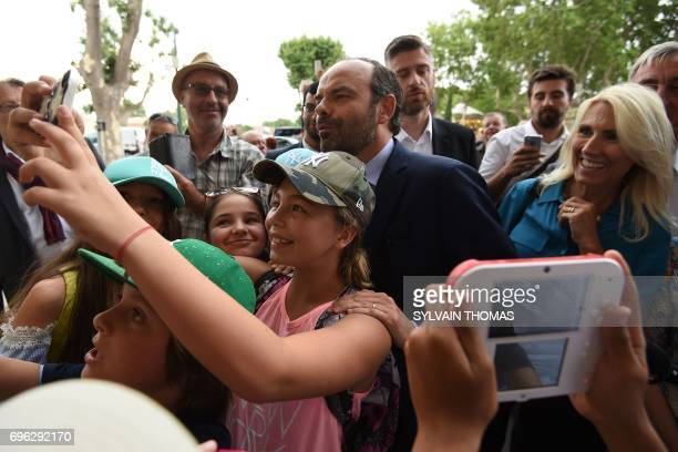 French Prime Minister Edouard Philippe takes selfies with children as he supports La Republique en marche party's candidate for the upcoming...