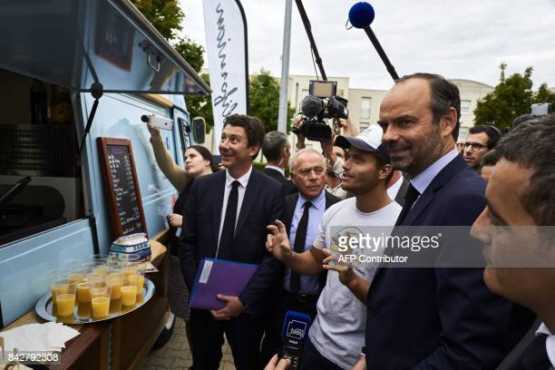 French Prime Minister Edouard Philippe together with French Junior Minister for Economy Benjamin Griveaux speak with managers of a Food Truck during...