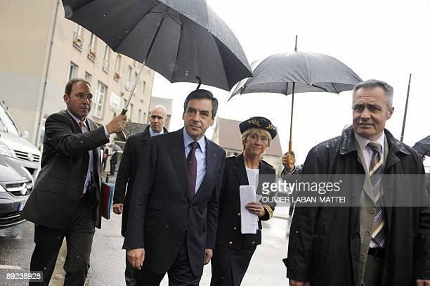 French Prime Minister Francois Fillon leaves the sousprefecture in ManteslaJolie west of Paris on July 24 next to the prefect of Yvelines Anne Boquet...