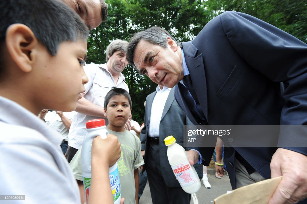 French Prime Minister Francois Fillon (R) receives milk bottles from a child on July 3, 2010 during the inauguration of the Agricultural Fair in Sable-sur-Sarthe, western France. Francois Fillon is President of the local Agricultural Committee located in his constituency.