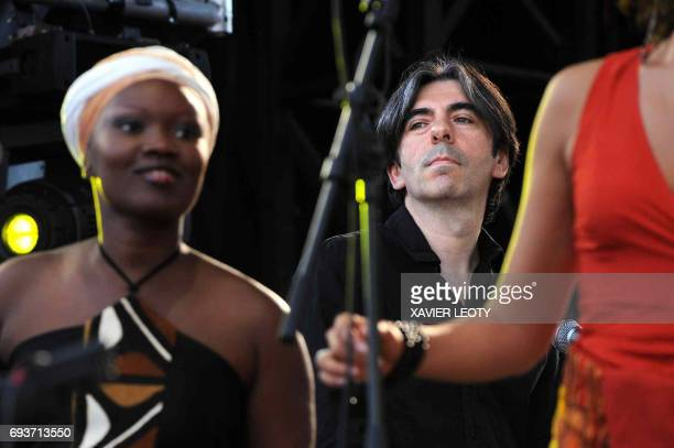 French Prime Minister Francois Fillon's brother pianist and orchestra conductor Dominique Fillon of the Dom Tom Folies band performs on stage on July...
