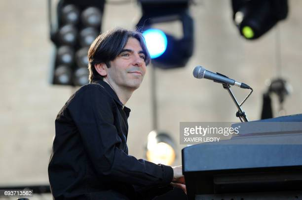 French Prime Minister Francois Fillon's brother pianist and orchestra conductor Dominique Fillon performs on the stage of the Francofolies music...