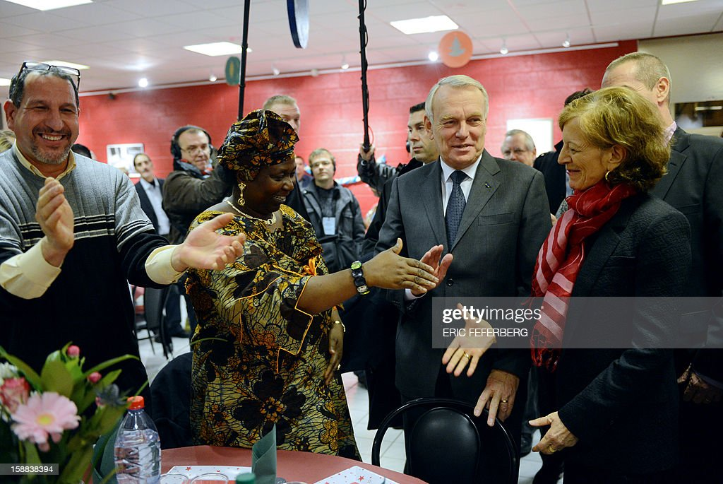 French Prime Minister Jean Marc Ayrault (2ndR) and his wife Brigitte Ayrault (2ndL) are welcomed on December 31, 2012 in Paris, by people who take part in the traditional New year's Eve dinner organized by French charity organization, 'Les petits freres des pauvres' who takes care of poor people. FEFERBERG