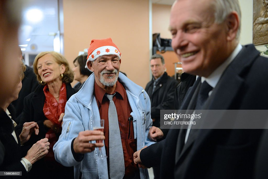 French Prime Minister Jean Marc Ayrault (R) and his wife Brigitte Ayrault (L) speak with people, on December 31, 2012 in Paris, as they visit during the traditional New year's Eve dinner, a center ruled by French charity organization, 'Les petits freres des pauvres' who takes care of poor people. FEFERBERG