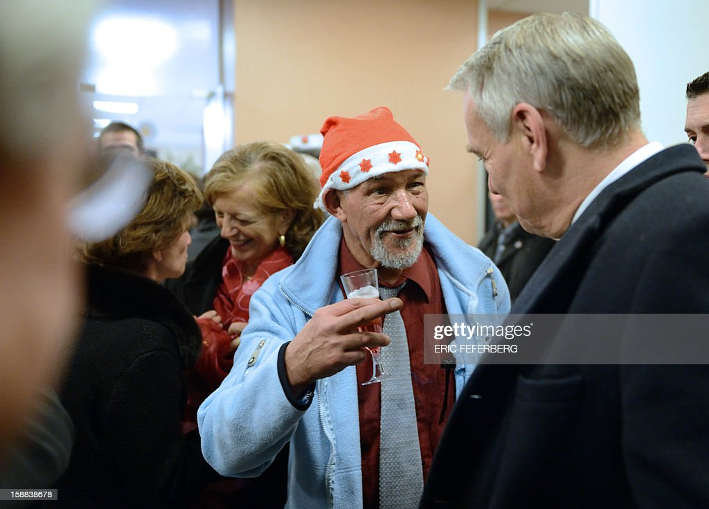 French Prime Minister Jean Marc Ayrault (R) flanked by his wife Brigitte Ayrault (2ndL) listens to a man, on December 31, 2012 in Paris, as they visit during the traditional New year's Eve dinner, a center ruled by French charity organization, 'Les petits freres des pauvres' who takes care of poor people. FEFERBERG