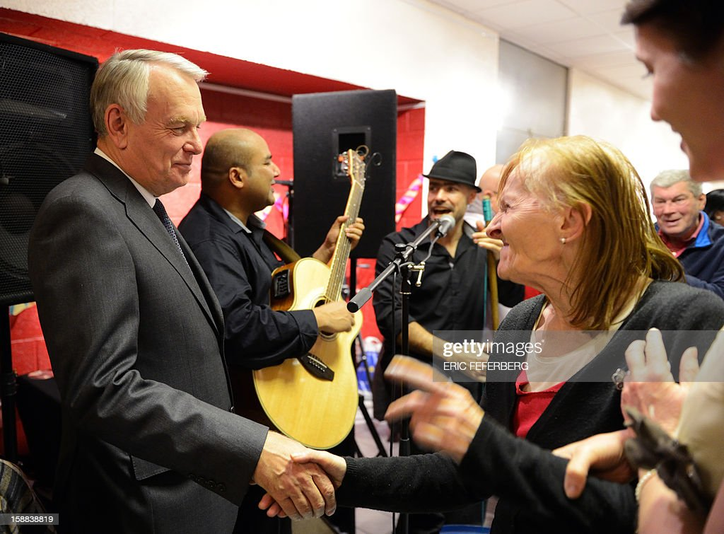 French Prime Minister Jean Marc Ayrault (L) is welcomed on December 31, 2012 in Paris, by people who take part in the traditional New year's Eve dinner at a center managed by French charity 'Les petits freres des pauvres', which takes care of poor people.