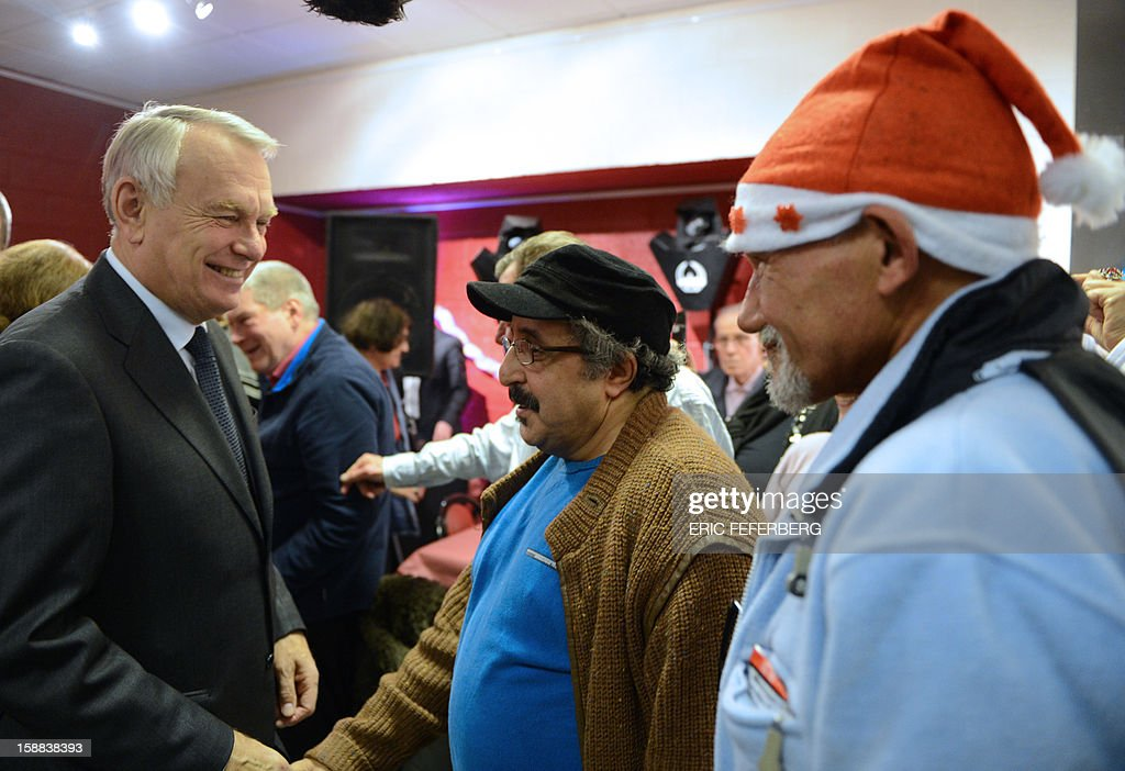 French Prime Minister Jean Marc Ayrault (L) shakes hand, on December 31, 2012 in Paris, with people who take part in the traditional New year's Eve dinner organized by French charity organization, 'Les petits freres des pauvres' who takes care of poor people. FEFERBERG