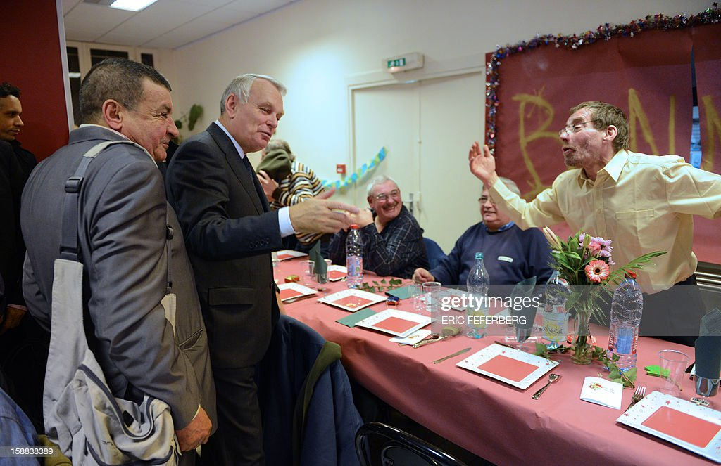 French Prime Minister Jean Marc Ayrault (2ndL) speaks, on December 31, 2012 in Paris, with people who take part in the traditional New year's Eve dinner organized by French charity organization, 'Les petits freres des pauvres' who takes care of poor people. FEFERBERG