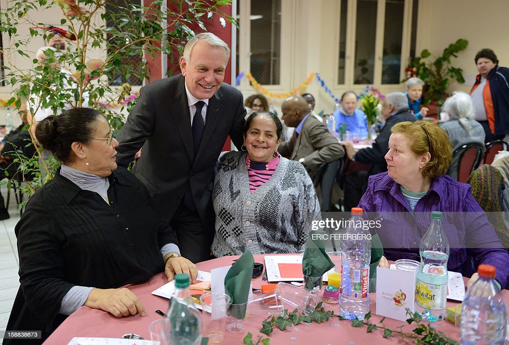 French Prime Minister Jean Marc Ayrault (2ndL) speaks, on December 31, 2012 in Paris, with women who take part in the traditional New year's Eve dinner organized by French charity organization, 'Les petits freres des pauvres' who takes care of poor people. FEFERBERG