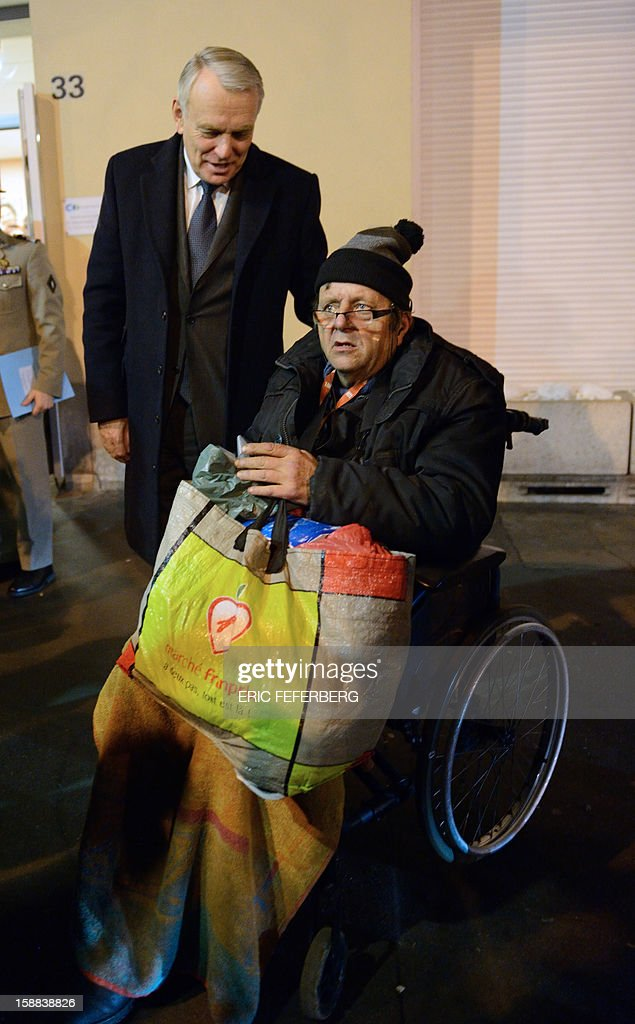 French Prime Minister Jean Marc Ayrault (L) speaks with a disabled man on December 31, 2012 in Paris, during the traditional New year's Eve dinner at a center managed by French charity 'Les petits freres des pauvres', which takes care of poor people.