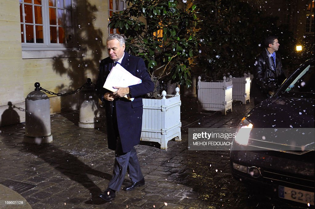 French Prime Minister Jean Marc Ayrault walks under snow as he arrives on January 14, 2013 at the Hotel Matignon in Paris, for a meeting to inform leaders of French political parties on France's military intervention in Mali. France launched its operation against Mali-based Islamists on a unilateral basis on January 11, but has since been offered logistical support by several NATO allies, including Belgium, Britain, Denmark, Germany and the United States.