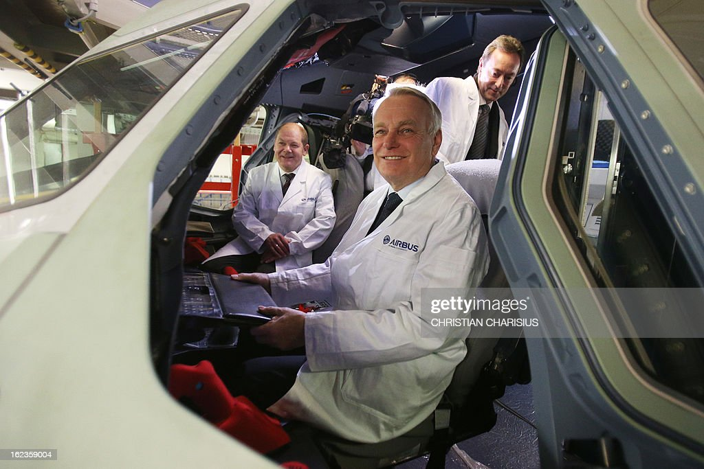 French Prime Minister Jean-Marc Ayrault (c) accompanied by Hamburg's First Mayor Olaf Scholz (L) and Airbus president and CEO Fabrice Bregier (R) poses inside a cockpit of an A380 airbus of Korean airlines 'Korean Air' during a visit to the final assembly line of the Airbus A380 on February 22, 2013 in Hamburg. Ayrault is on a visit to Hamburg participating on the traditional Matthiae-Mahl.