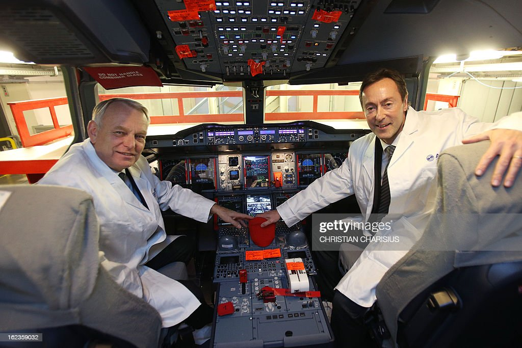 French Prime Minister Jean-Marc Ayrault (L) and Airbus president and CEO Fabrice Bregier (R) pose inside a cockpit of an A380 airbus of Korean airlines 'Korean Air' during a visit to the final assembly line of the Airbus A380 on February 22, 2013 in Hamburg. Ayrault is on a visit to Hamburg participating on the traditional Matthiae-Mahl.