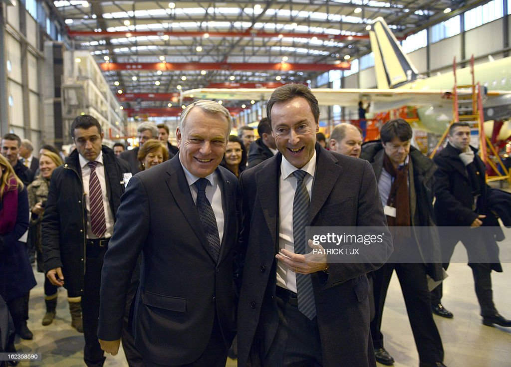 French Prime Minister Jean-Marc Ayrault (L) and Fabrice Bregier, president and CEO of aircraft manufacturer Airbus, walks through the final A320 airplane assembly line on February 22, 2013 in Hamburg. Ayrault is on a visit to Hamburg participating on the traditional Matthiae-Mahl. AFP PHOTO / PATRICK LUX