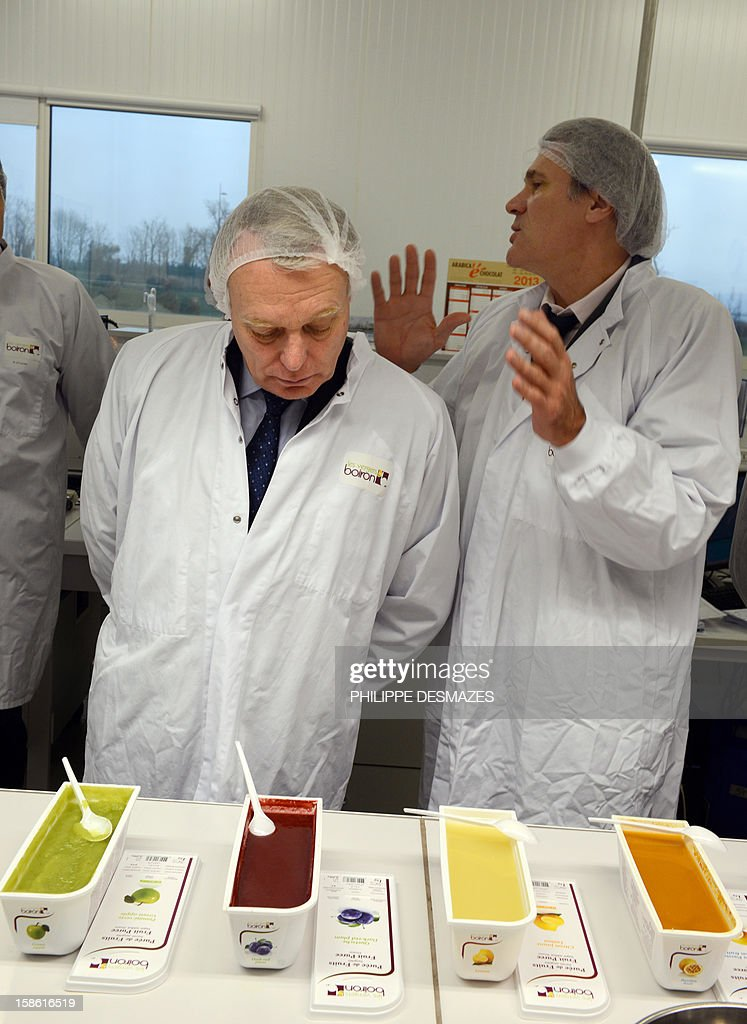 French Prime Minister, Jean-Marc Ayrault (L) and French Agriculture Minister Stephane Le Foll (R) look at vegetables and fruits purees made in 'Les vergers Boiron' company in Chatauneuf-sur-Isere as part to a visit on the theme of agriculture on December 21, 2012, in the Valence region, southeastern France.