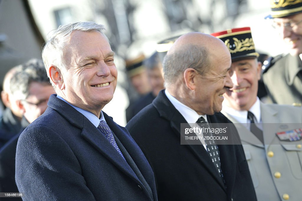 French Prime minister Jean-Marc Ayrault (L) and French Defence Minister Jean-Yves Le Drian (R) smile as they review troops of the 2nd Engineer French Foreign Legion Regiment, on December 17, 2012 in Clermont-Ferrand, central France, during a ceremony marking the dissolution of a joint tactical bataillon that served in Afghanistan from May to November 2012. France joined the NATO coalition in late 2001 to help prop up the new government against an insurgency, which began after a US-led invasion toppled the Taliban government earlier that year for giving refuge to Osama bin Laden and his Al-Qaeda network, following the 9/11 attacks on New York and Washington. ZOCCOLAN