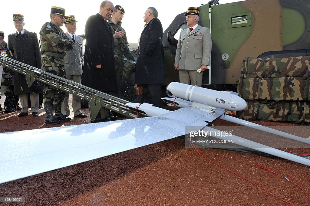 French Prime minister Jean-Marc Ayrault (2ndR) and French Defence Minister Jean-Yves Le Drian (4thL) listen to a military as they look the tactical mini drone DRAC (drone de renseignement au contact) during a visit of the 2nd Engineer French Foreign Legion Regiment, on December 17, 2012 in Clermont-Ferrand, central France, during a ceremony marking the dissolution of a joint tactical bataillon that served in Afghanistan from May to November 2012. France joined the NATO coalition in late 2001 to help prop up the new government against an insurgency, which began after a US-led invasion toppled the Taliban government earlier that year for giving refuge to Osama bin Laden and his Al-Qaeda network, following the 9/11 attacks on New York and Washington.
