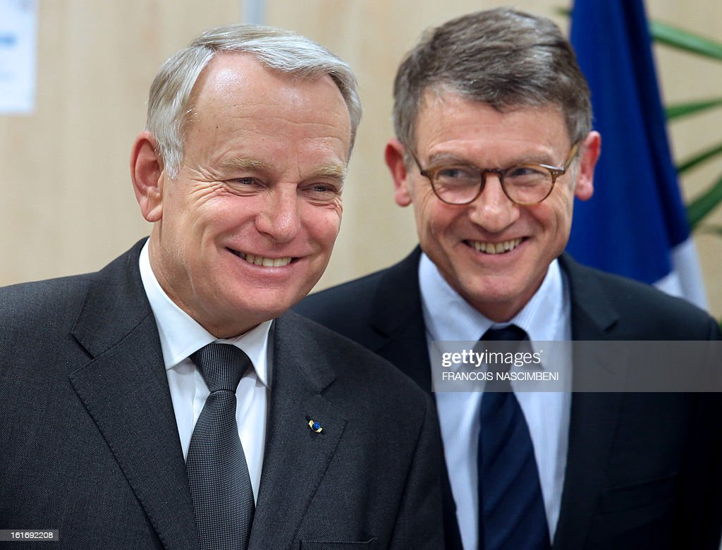 French Prime Minister Jean-Marc Ayrault (L) and French Education Minister Vincent Peillon react during their visit to the Colbert high school in Reims, eastern France, on February 14, 2013, before signing agreements for the 'Future Professional Jobs' (Emploi d'Avenir Professionnel, EAP in French).
