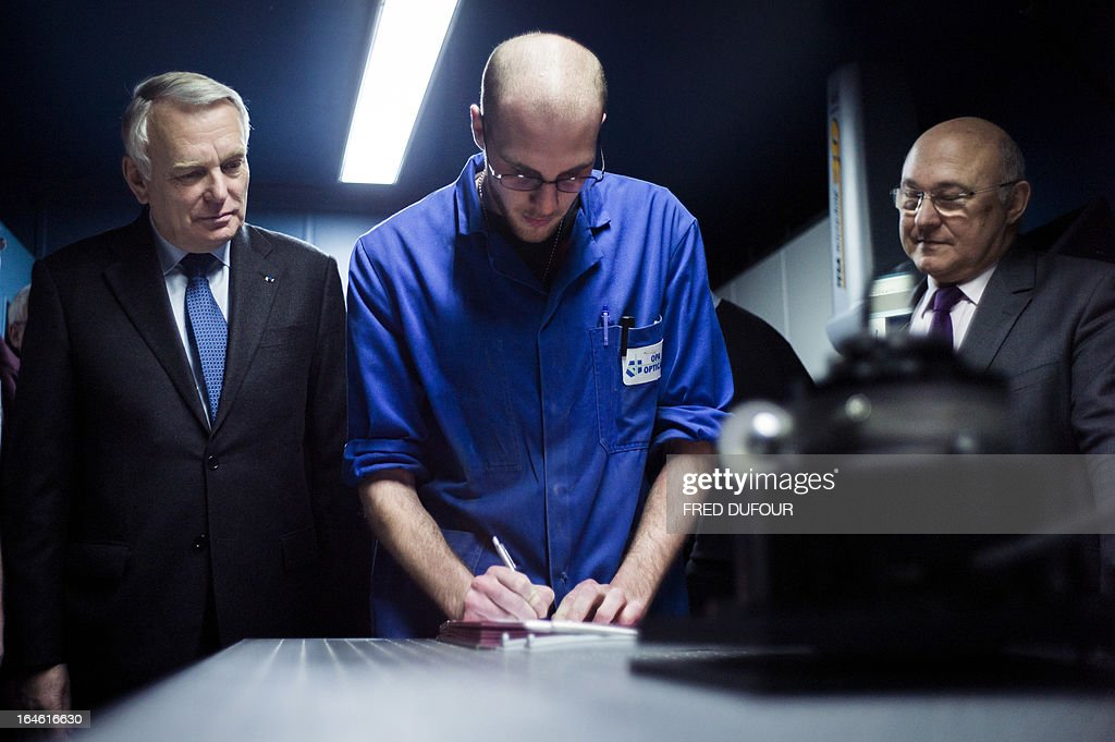 French Prime Minister Jean-Marc Ayrault (L) and French Labour, Employment and Social Dialogue Minister, Michel Sapin (R) stand beside a young man signing a 'generation contract' at the OPA-OPTICAD, an optical production and assembling company specialized in lazer and optical systems, on March 25, 2013 in Mitry-Mory, North East of Paris, during their visit focused on employment.