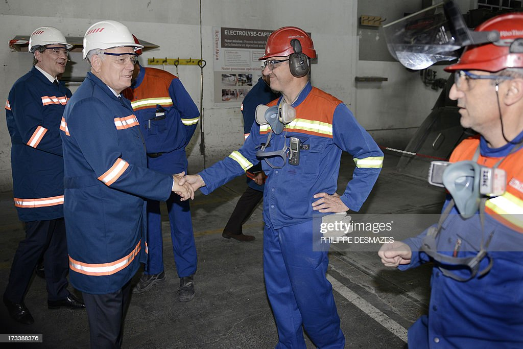 French Prime minister Jean-Marc Ayrault (2ndL) and French Minister for Industrial Renewal and Food Industry Arnaud Montebourg (L) shake hands with workers as they visit the Rio Tinto Alcan (RTA) aluminum factory in Saint-Jean-de-Maurienne, southeast of France, on July 13, 2013. Heads of Rio Tinto Alcan and Germany's Trimet met today in Paris regarding the take over of RTA by Trimet which could save 510 jobs at the two sites of Saint-Jean-de-Maurienne and Castelsarrasin.