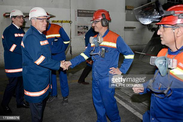French Prime minister JeanMarc Ayrault and French Minister for Industrial Renewal and Food Industry Arnaud Montebourg shake hands with workers as...