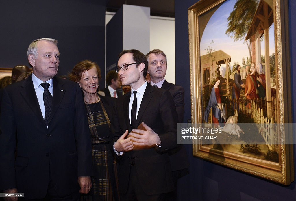French Prime Minister Jean-Marc Ayrault (L) and his wife Brigitte listen to a curator on March 26, 2013 as they visit the exhibition 'De l'Allemagne, 1800-1939 - From Friedrich to Beckmann' at the Louvre museum in Paris . AFP PHOTO / POOL / BERTRAND GUAY