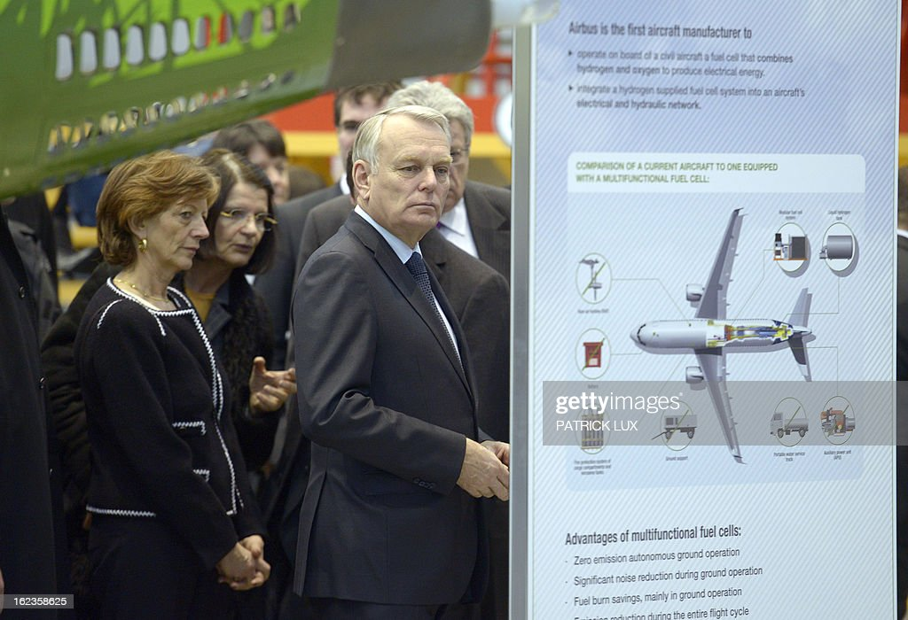 French Prime Minister Jean-Marc Ayrault (R) and his wife Brigitte receive an explanation at the final assembly line of the A320 airplane on February 22, 2013 in Hamburg. Ayrault is on a visit to Hamburg participating on the traditional Matthiae-Mahl.