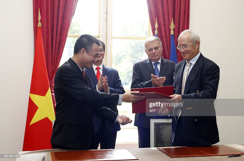 French Prime minister Jean-Marc Ayrault (2ndR) and Vietnam's Prime minister Nguyen Tan Dung (2ndL) applaud after Air France contracts' director Christophe Mouret (R) and VietJetAir deputy commercial director Luu Duc Khanh (L) signed a letter of intent with Airbus to purchase 62 A320 medium-haul aircraft and take options on another 30, on September 25, 2013 at the Hotel Matignon in Paris.