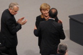 French Prime Minister JeanMarc Ayrault applauds as French President Francois Hollande is cheered by German Chancellor Angela Merkel after his speech...
