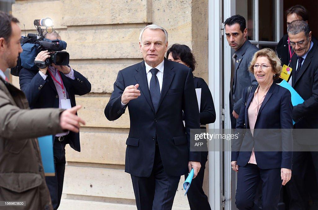 French Prime minister Jean-Marc Ayrault arrive (C) arrives flanked by French Minister for Higher Education and Research Genevieve Fioraso (R), on November 26, 2012 at the elite research institution College de France in Paris, to take part in the opening of the meeting for Higher Education and Research.